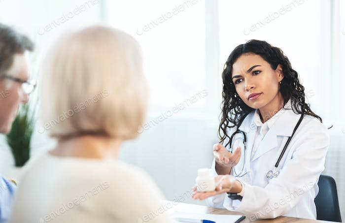 Angry brazilian nurse giving pills to mature patients