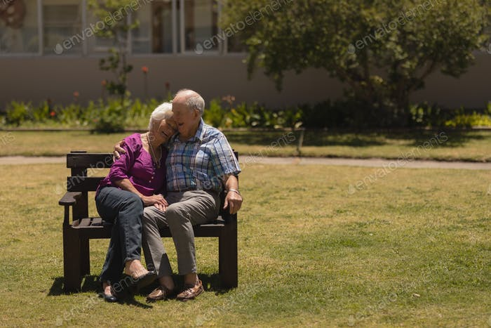 Front view of active senior couple sitting together on the bench in the park