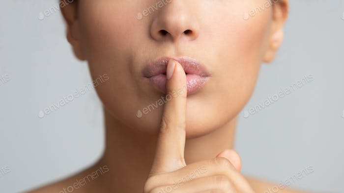 Women's secret. Woman holding finger on lips