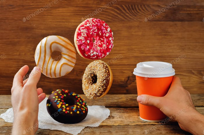 Men's hand with flying donuts and coffee