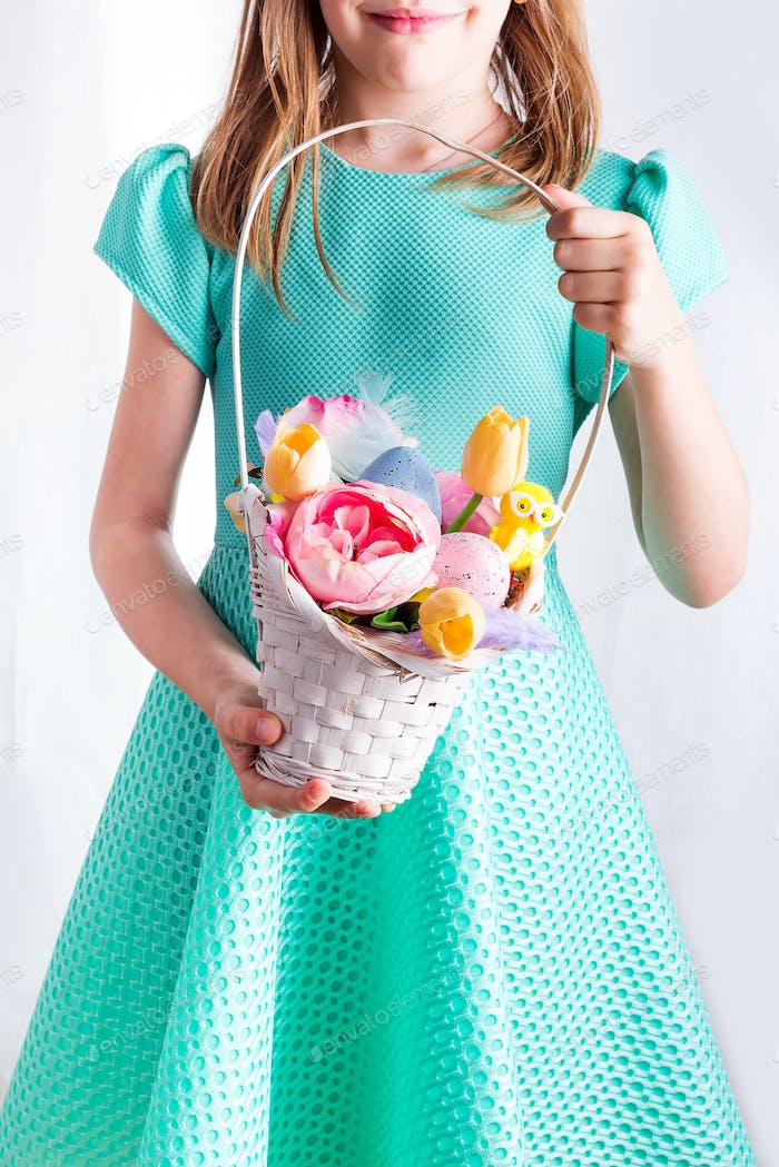 Cute little child holding basket with painted eggs and flowers on Easter day.