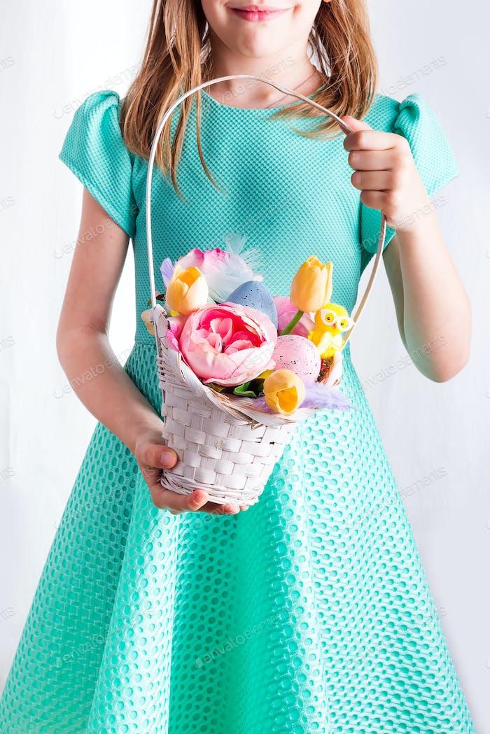Süßer kleiner Kinderkorb mit bemalten Eiern und Blumen am Ostertag.