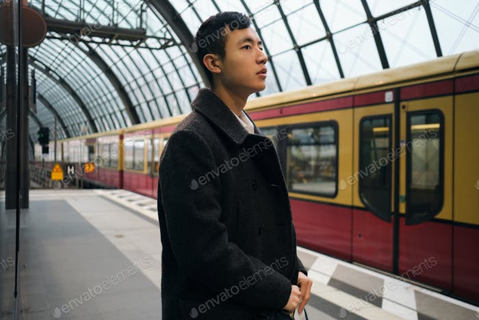 Side view of young Asian businessman in coat thoughtfully waiting train at city subway station