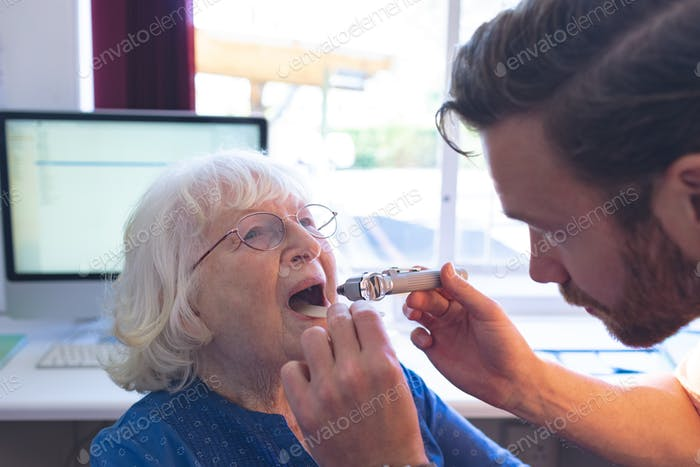 Side view of male Caucasian doctor checking senior female patient mouth with otoscope in clinic