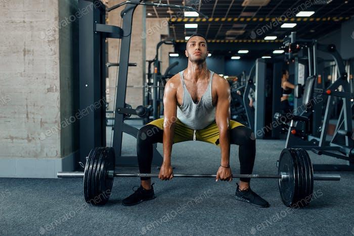 Атлетический человек делает упражнения со штангой в тренажерный зал