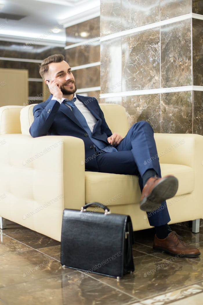 Handsome Businessman Speaking by Phone in Lobby
