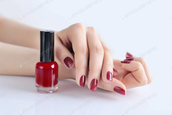 Hands of a woman with dark red manicure and nail polish bottle