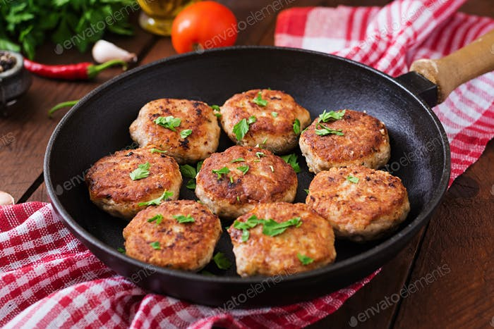Juicy delicious meat cutlets in pan on a wooden table.