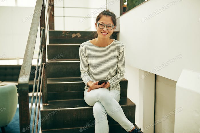 Smiling Asian businesswoman sitting with her cellphone on office stairs