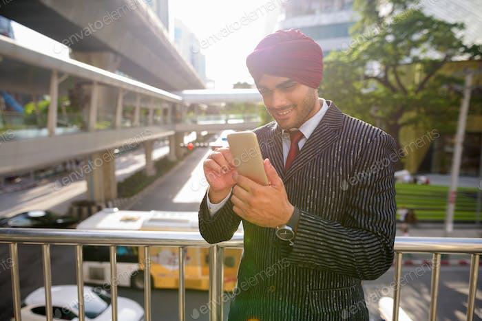 Indian businessman outdoors in city using phone with lens flare