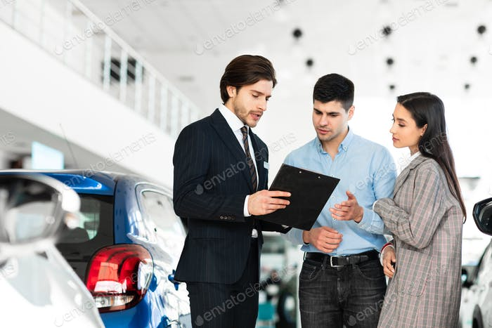 Spouses buying car consulting with dealer guy
