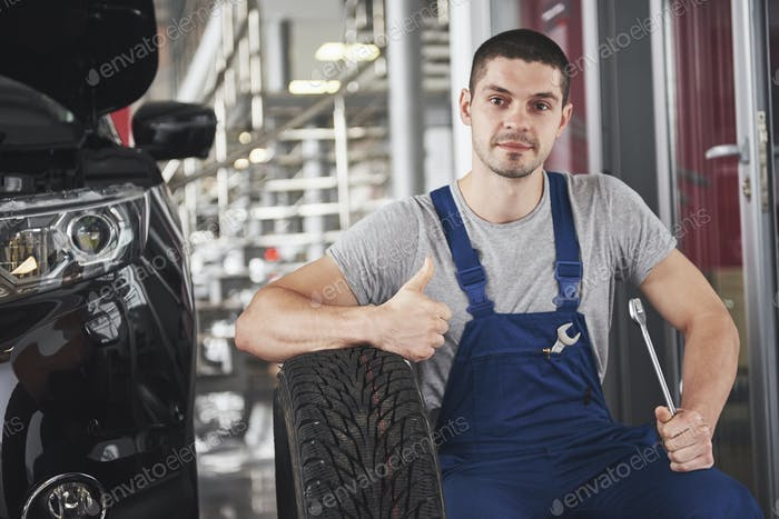 Close up of mechanic showing ok gesture with his thumb while holding a wrench