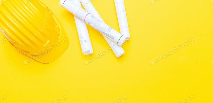 Project paper blueprints and hard hat on yellow color background, copy space
