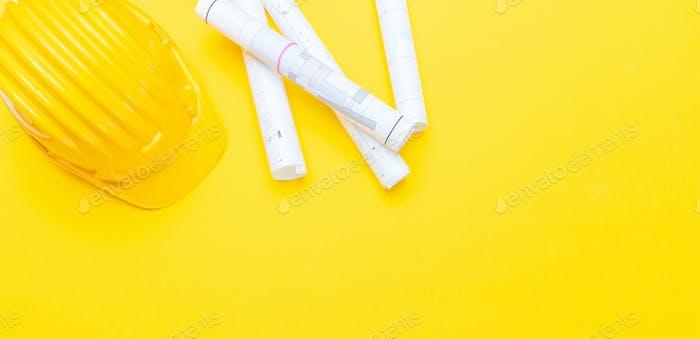Projektpapier-Blueprints und harter Hut auf gelbem Hintergrund, Kopierraum