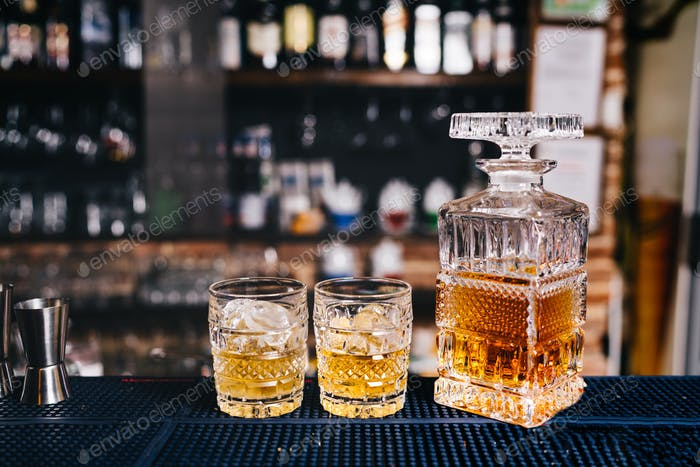 Two crystal glasses on bar counter with wiskey and ice