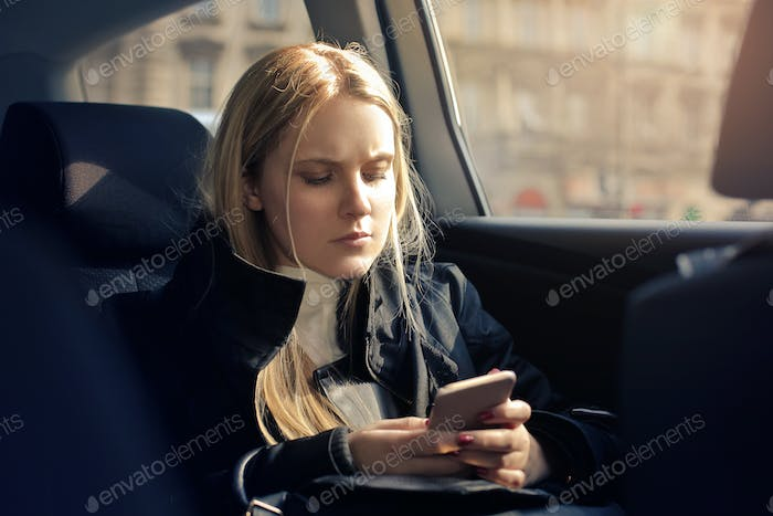 Girl using a smartphone in a car