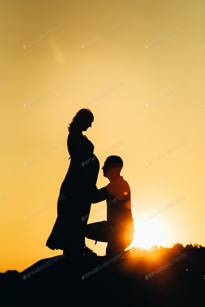 silhouettes of a happy young happy family against an orange sunset