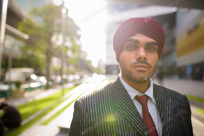 Portrait of Indian businessman outdoors in city with lens flare