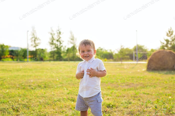 Happy laughing baby boy playing on summer or autumn field.