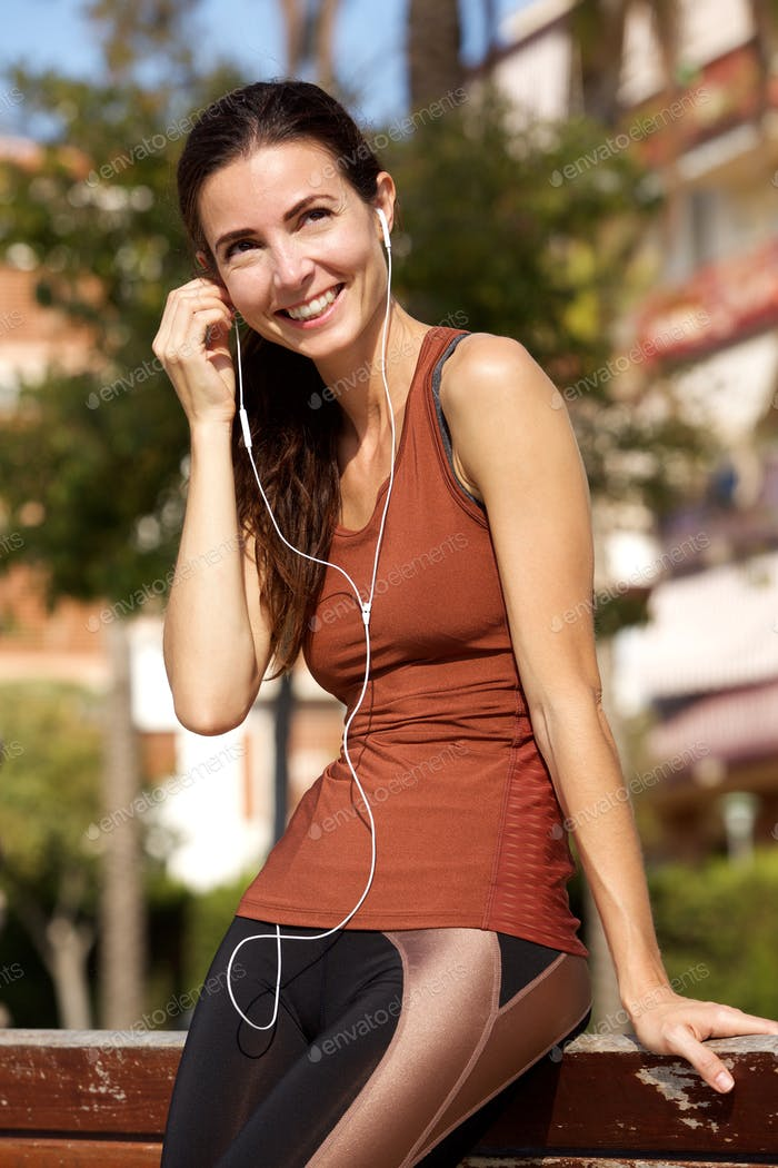 Attractive sporty woman resting after morning run and adjusting earphones