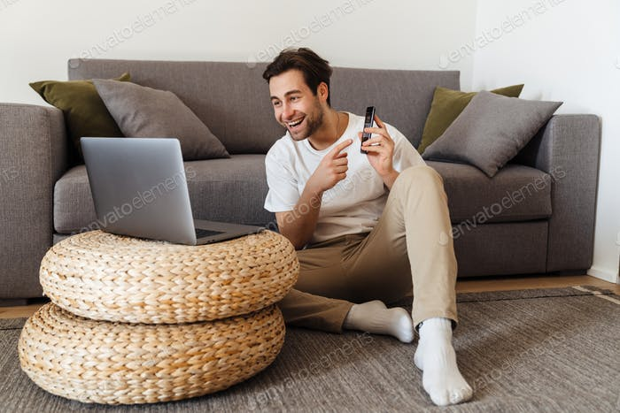 Smiling brunette man sitting on the floor with laptop