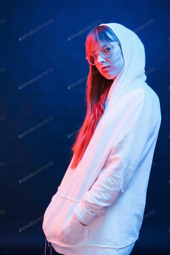 Hood on the head. Studio shot in dark studio with neon light. Portrait of young girl