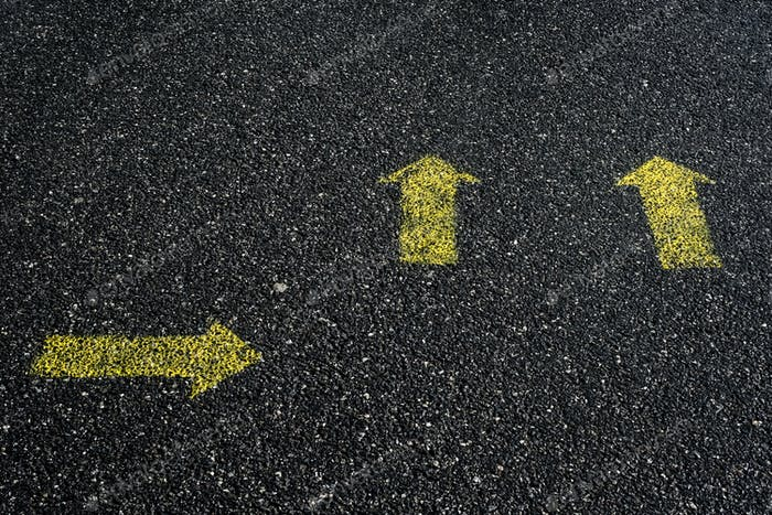 High angle close up of yellow arrow symbols painted on asphalt ground.