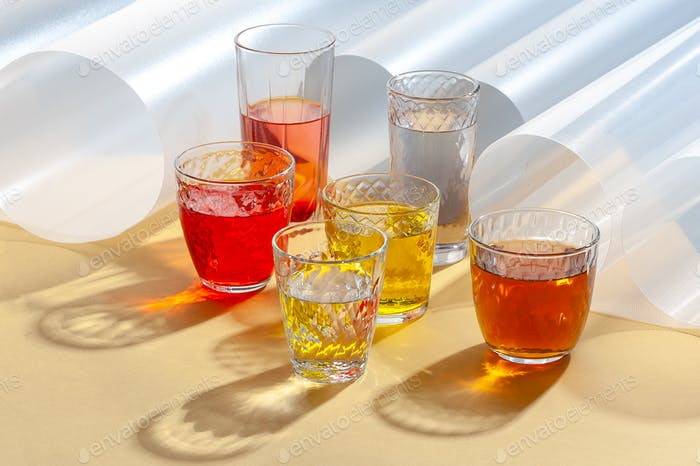 Colored drinks in glass cups on a yellow background with additio