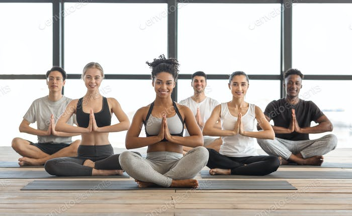 Wellness Concept. Happy Multicultural Young People Practicing Yoga In Modern Light Studio
