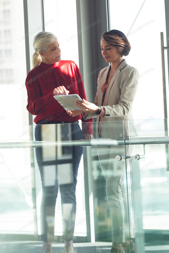 Front view of mixed race businesswomen discussing over digital tablet in modern office building