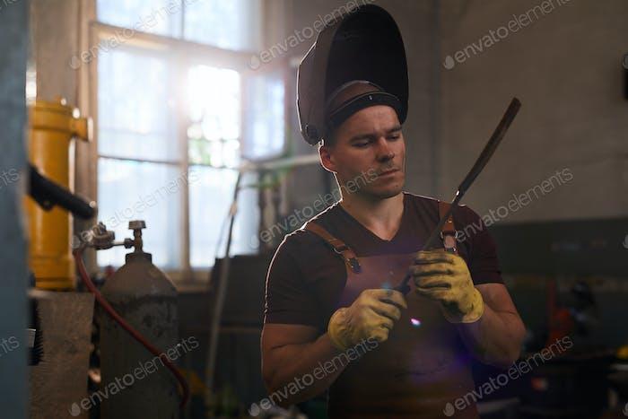 Checking metal bar in workshop