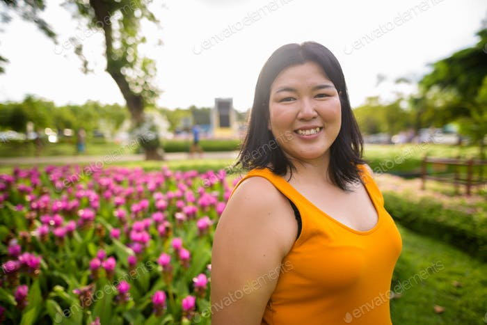 Happy overweight Asian woman relaxing at the park