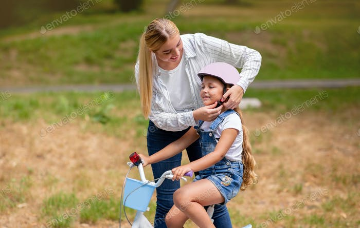 Little Girl Learning To Ride Bicycle With Mother Outdoors