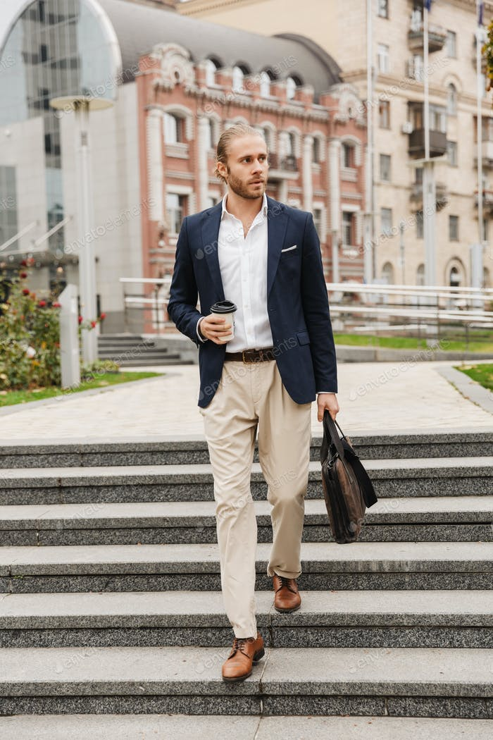 Image of young businessman holding coffee cup walking on city street