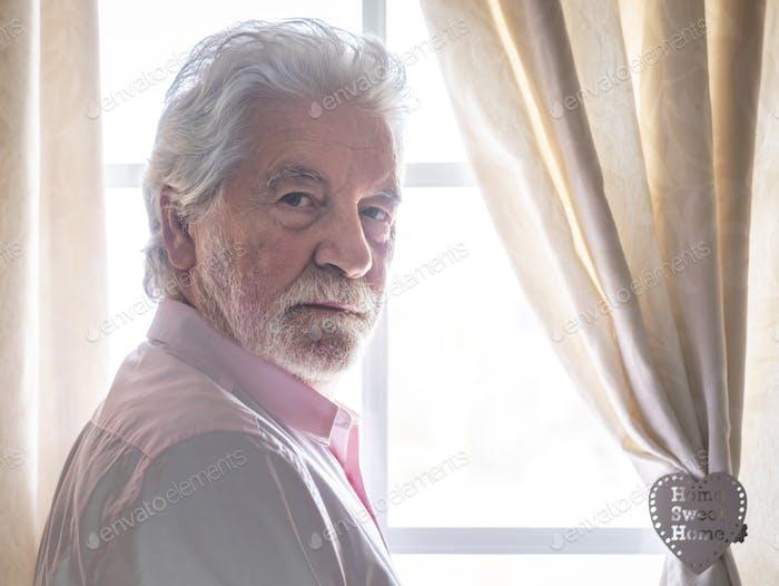Senior bleibt zur Quarantäne zu Hause, hinter dem Fenster, um eine Ansteckung durch COVID-19 zu vermeiden