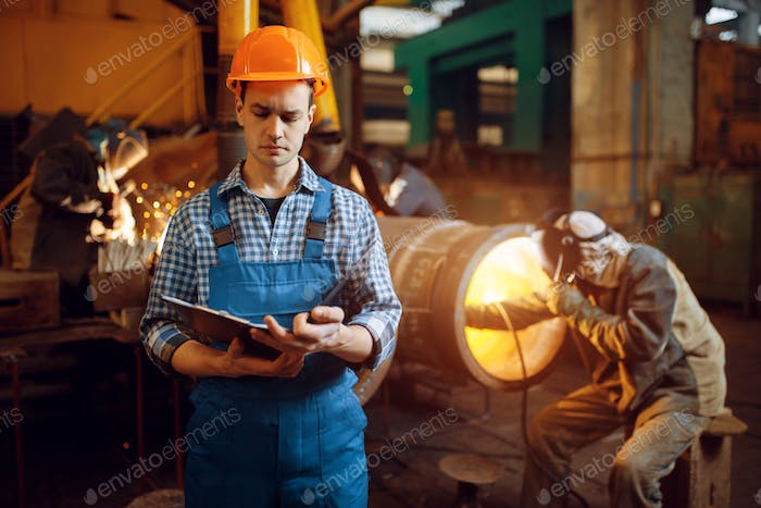 Master with notebook and welder on factory