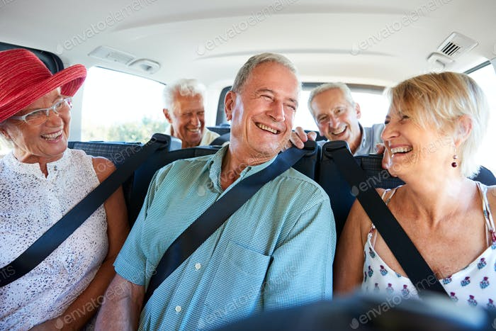 Group Of Senior Friends Sitting In Back Of Van Being Driven To Vacation