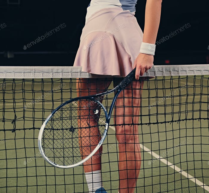 Sexy female tennis player posing on a tennis court.
