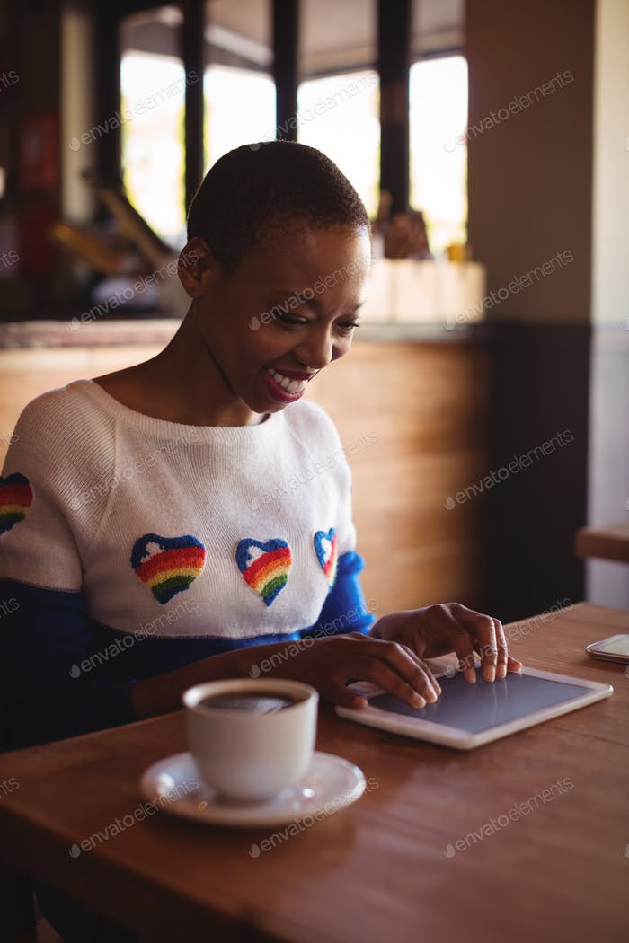 Happy woman using digital tablet while having coffee