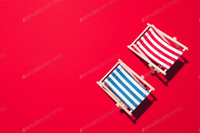 Flat lay of beach deck chairs on red background with copy space. Summer and travel concept. Creative