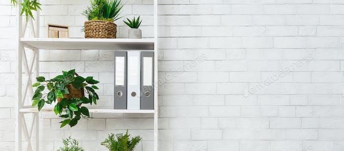 Weißes Bücherregal mit Pflanzen und Ordnern über der Wand