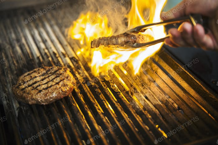 Close up of chef flame grilling a burger on a hot griddle.