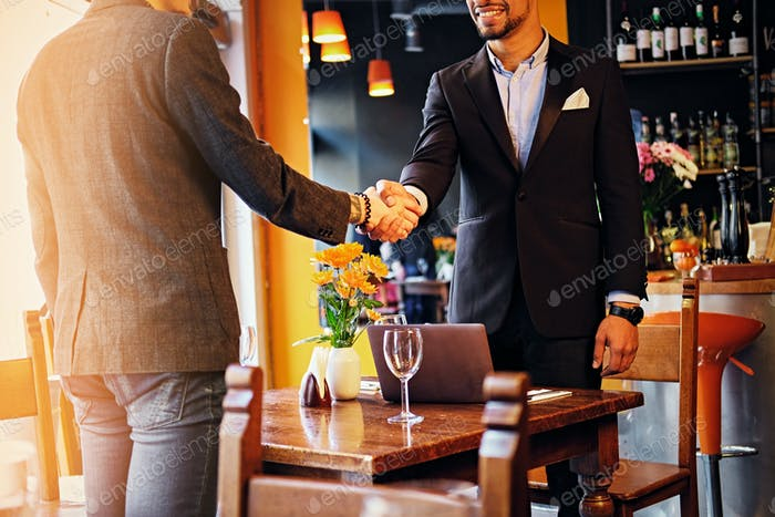Two men handshake in a restaurant.