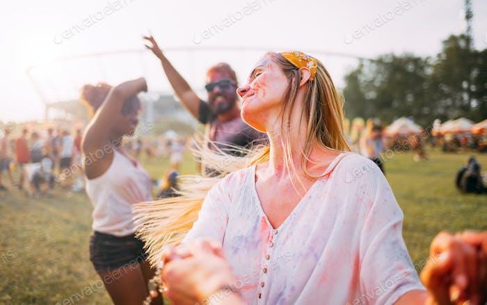 Mujer joven de pelo largo bailando con amigos en el festival de holi