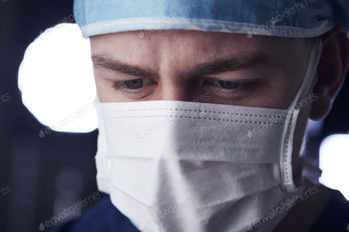 Male healthcare worker in scrubs, head shot, looking down