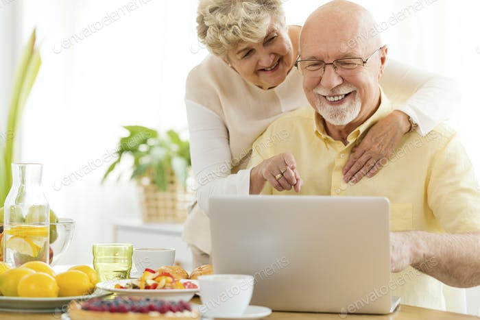 Smiling senior man using laptop with his happy wife. Elderly peo