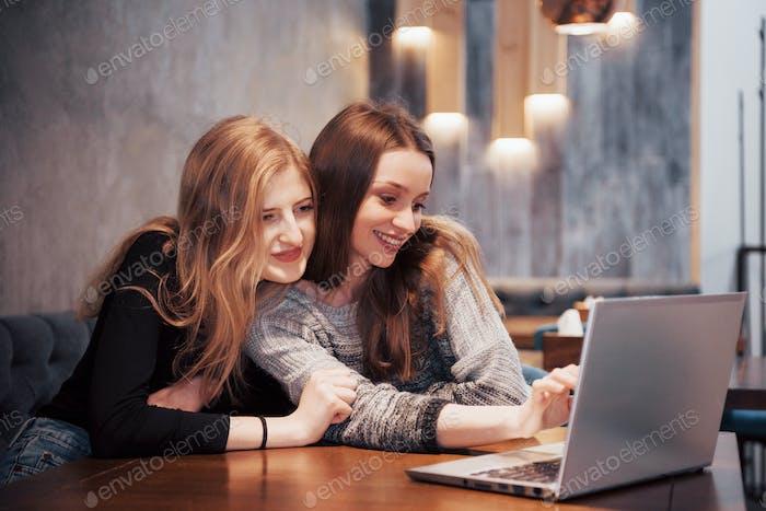 Dos chicas navegando por la red, publicando en las redes sociales en una computadora portátil y divirtiéndose
