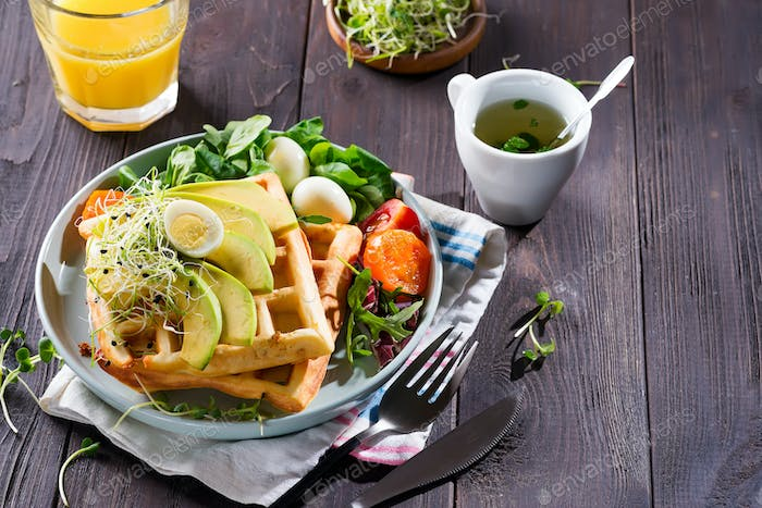 Healthy breakfast plate with homemade waffles, natural organic avocado, eggs and cup of mint tea on