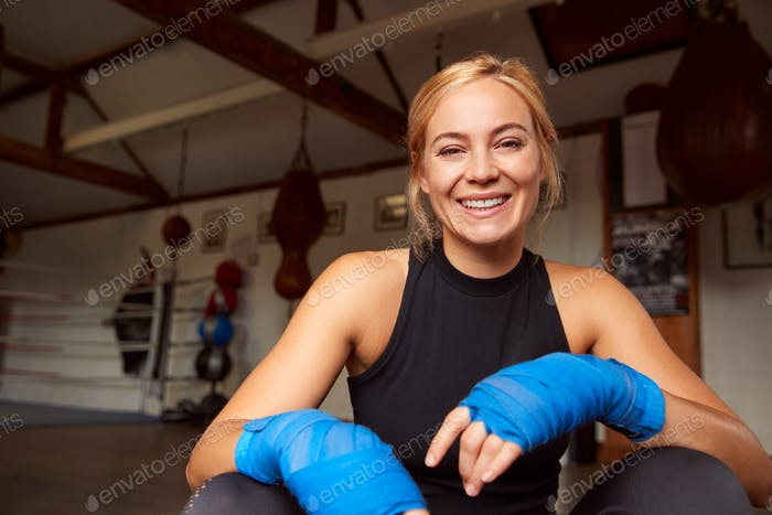 Portrait Of Female Boxer With Protective Wraps On Hands Training In Gym