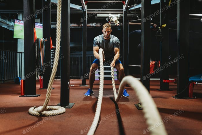 Fitness man working out with battle ropes at gym
